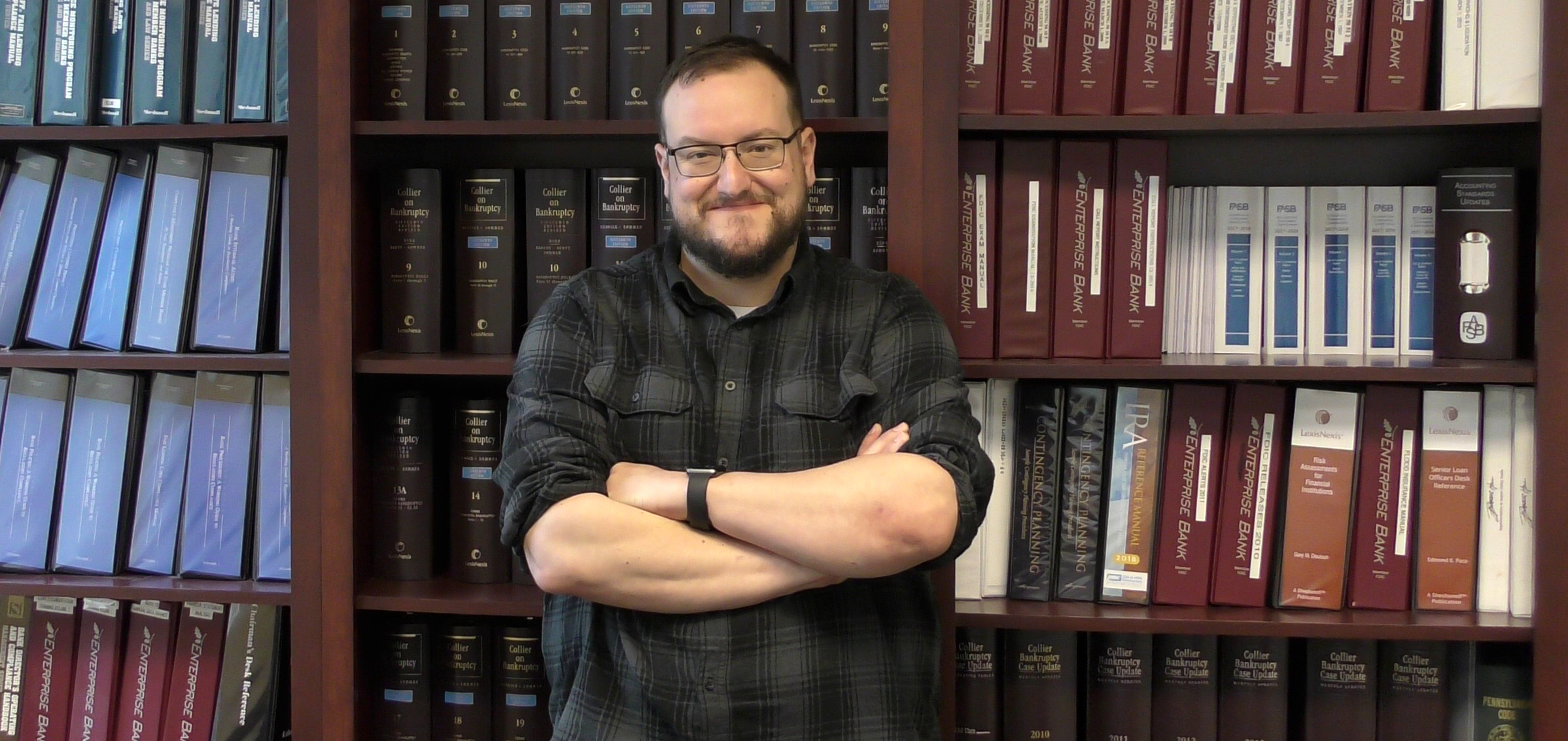A smiling gentleman stands with his arms crossed. He is wearing a flannel shirt, glasses, and he has a beard. He stands in front of a bookcase.