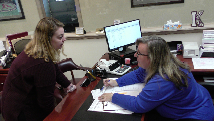Two women discuss financial matters over a desk